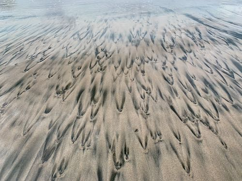 Black and tan sand patterns on Playa Pelada Costa Rica
