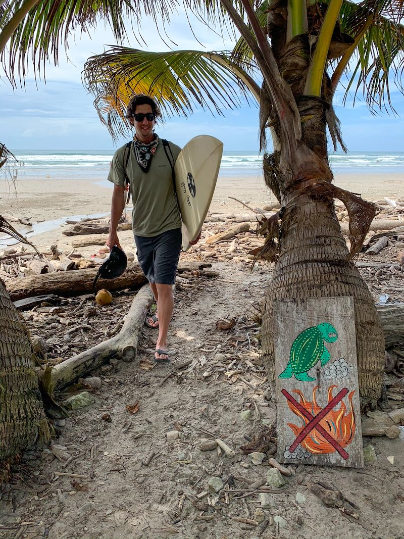 Walking with a surfboard in Costa Rica next to a sign explaining no beach fires because of sea turtle eggs